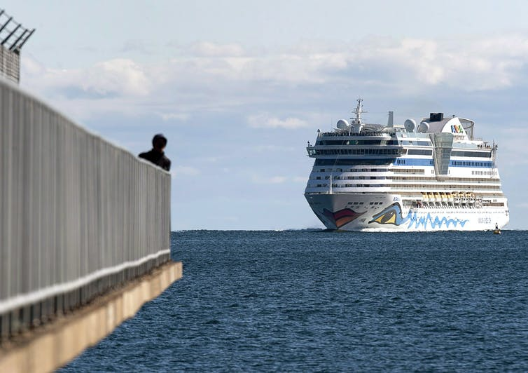 A huge cruise ship approaches a harbour as a person watches at the end of a pier in the foreground.