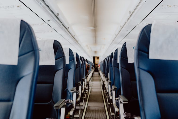 The empty interior of an airplane, with no passengers in any of the seats