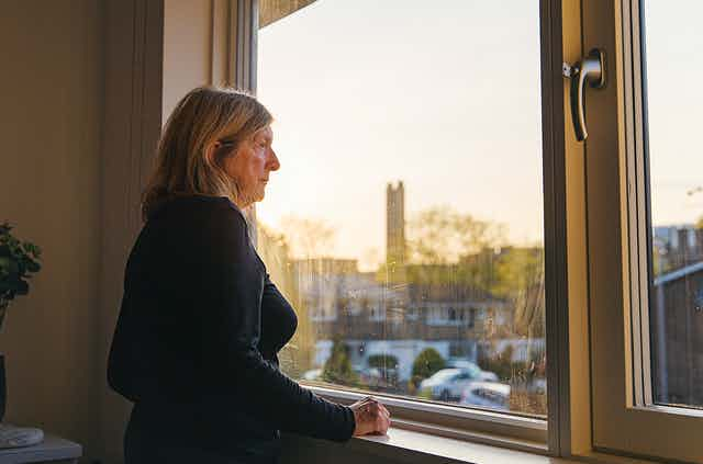 Older adult looking out a window.