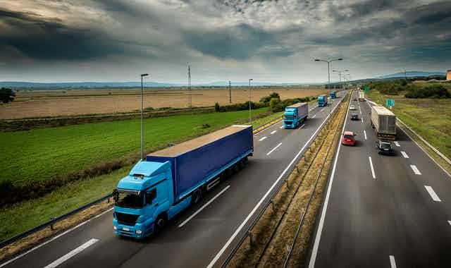 Transport trucks and cars on a four-lane highway
