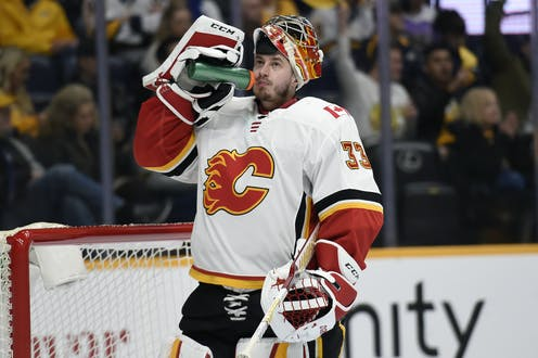 A Calgary Flames hockey player in a jersey with a flaming C drinks water.