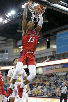 A basketball player dunks.
