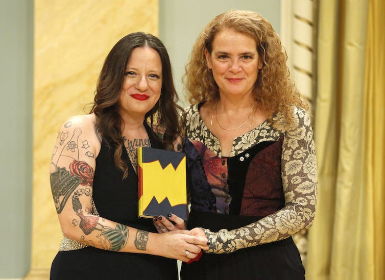 Governor General Julie Payette and author Cherie Dimaline pose for a photo at the Governor General's Literary Award for English young people's literature. Dimaline is holding a book in her left hand.