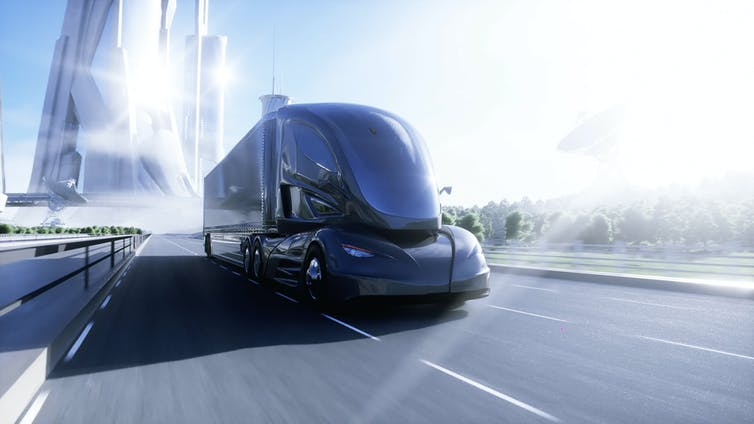 A futuristic electric truck on a highway near a city
