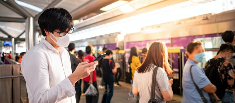 Grupo numeroso de personas con mascarillas esperando en el andén de una estación de metro