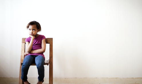 Bored child sitting in chair looking out into the distance.