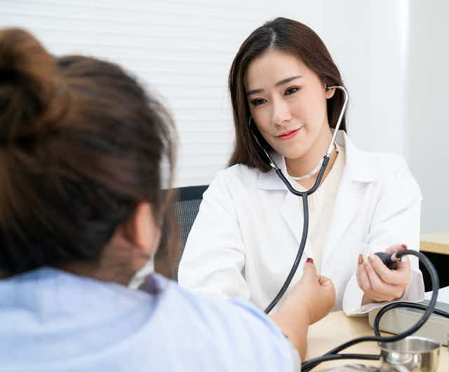 A doctor is taking her patient's blood pressure