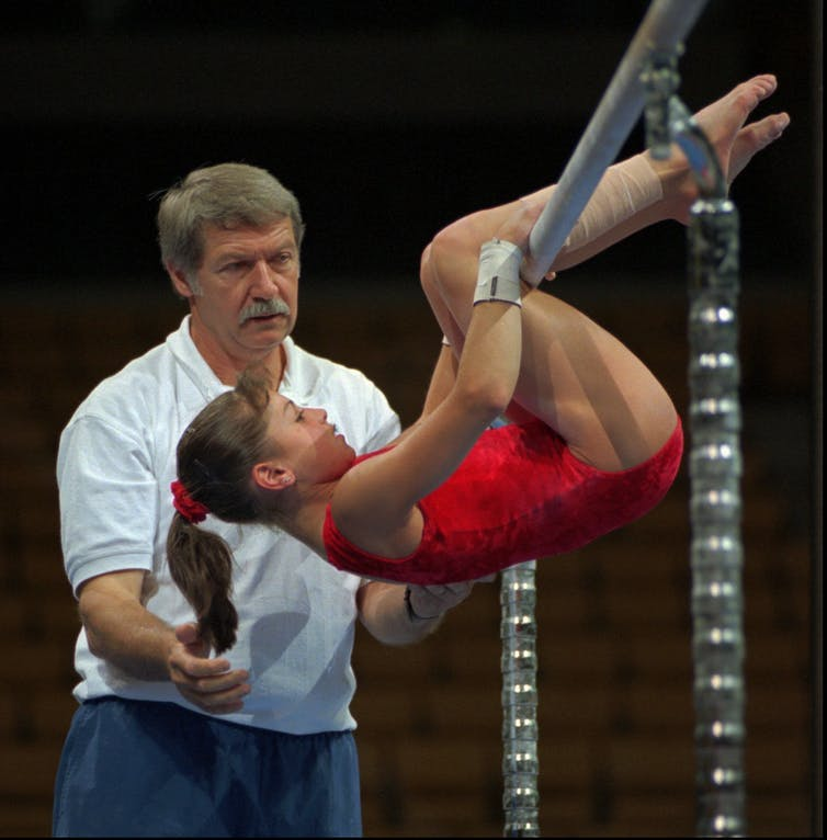 Young gymnast hangs on a bar, watched over by an older man.