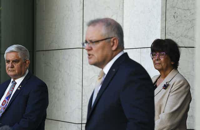 Minister for Indigenous Australians, Ken Wyatt stands with Prime Minister Scott Morrison and Aunty Pat Turner