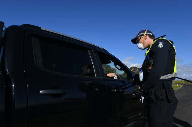 A police officer, wearing a face mask, questions a driver at the border