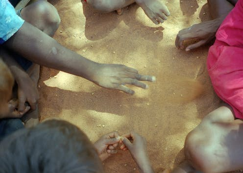 Hands of Indigenous Australians sitting in circle
