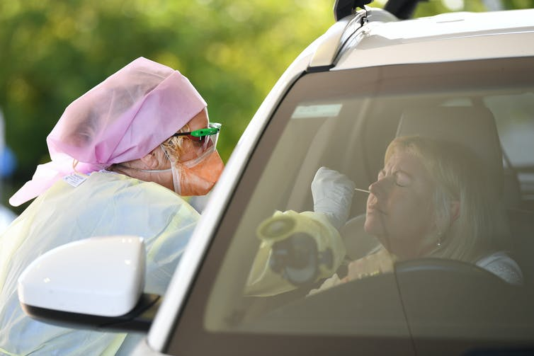 Woman in car receives a nasal swab from a health worker