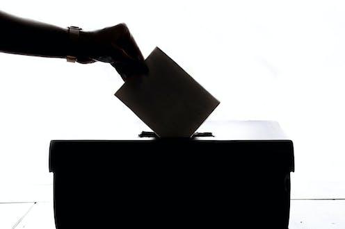 Main déposant une enveloppe dans une boîte, à contrejour.