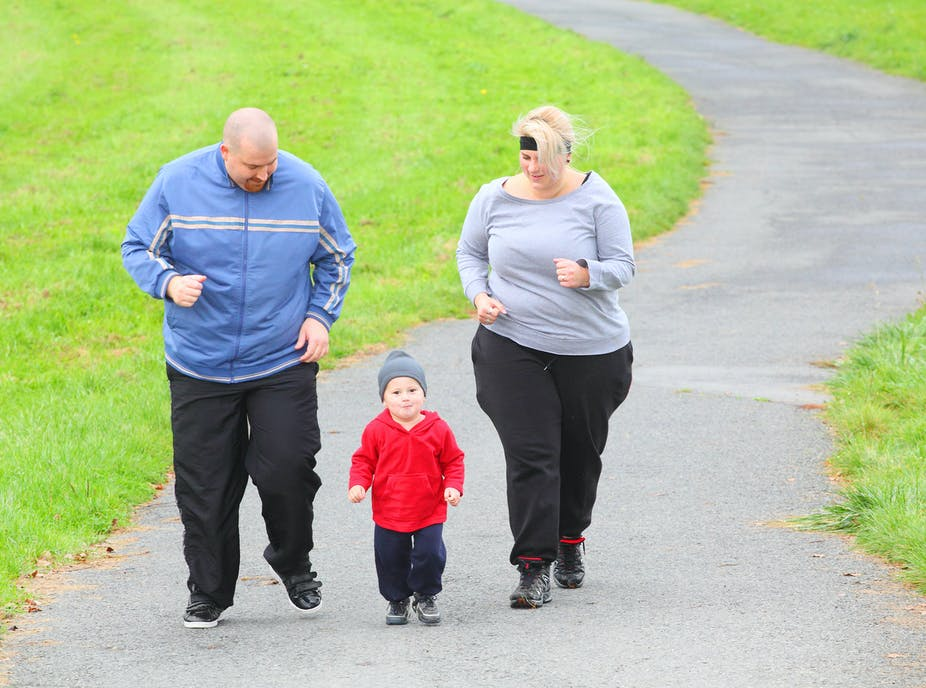 Overweight parents jog with their toddler.