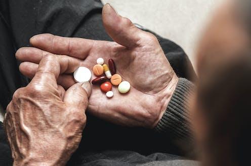 Ocho pastillas distintas en manos de una persona mayor.