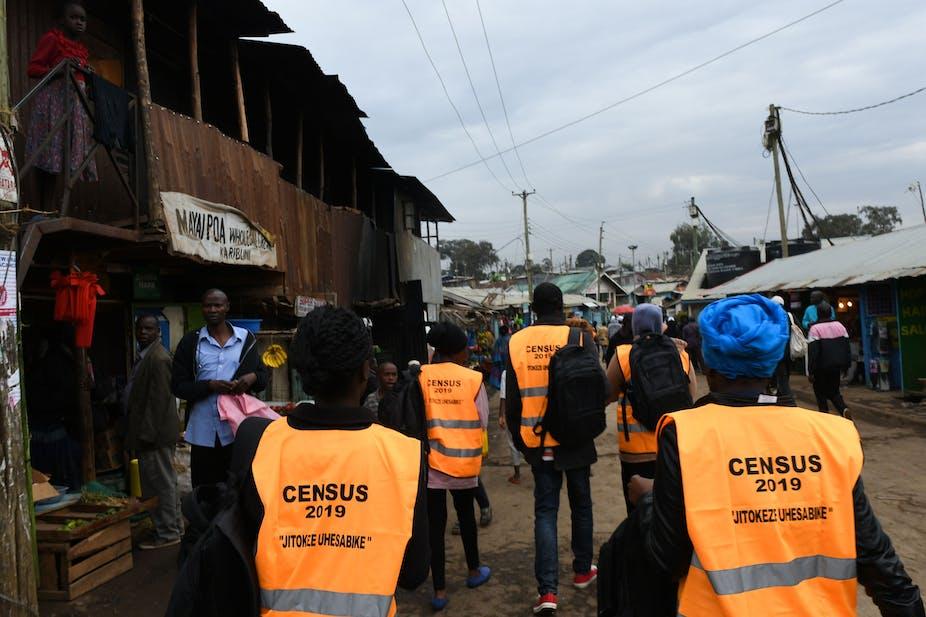 Census workers walk past vendors in a Nairobi street