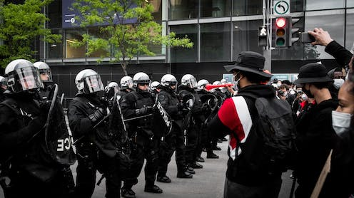 A row of police in riot gear face off against protestors.