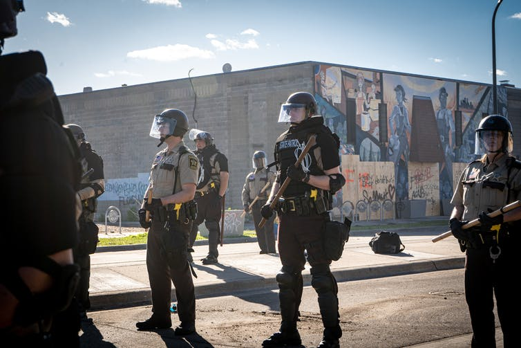 Armed police in riot gear stand in formation