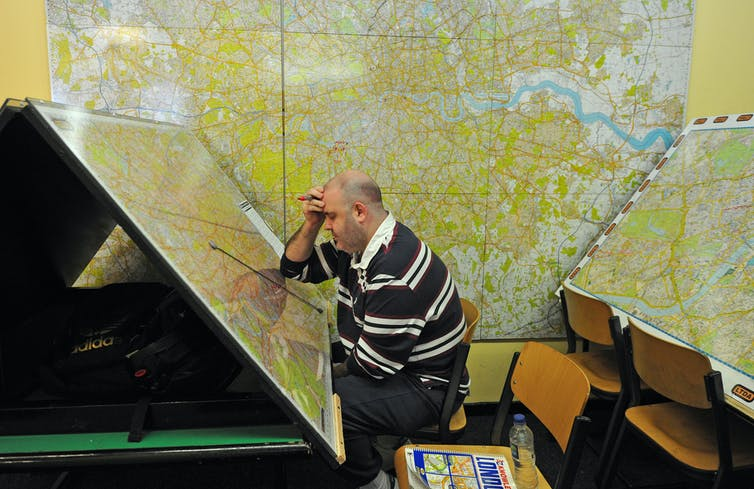 Man studying massive maps of London