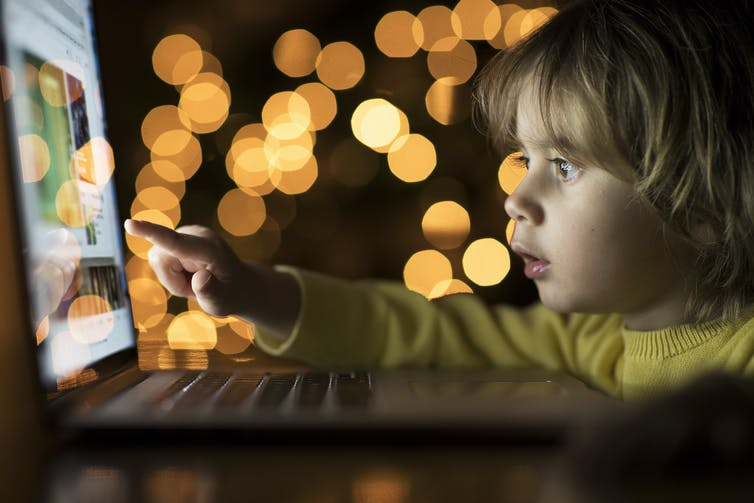 Toddler looks at a laptop in the dark.
