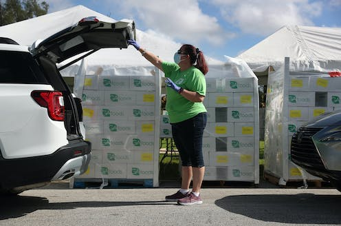 Loren Mennes place food in the back of a vehicle at a drive-thru food distribution site set up at the First Church of the Brethren on July 24 in Miami, Florida.