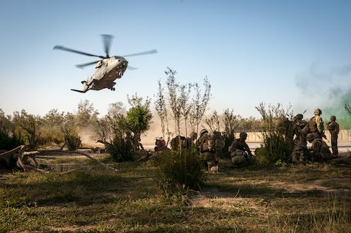 Military helicopter landing near troops