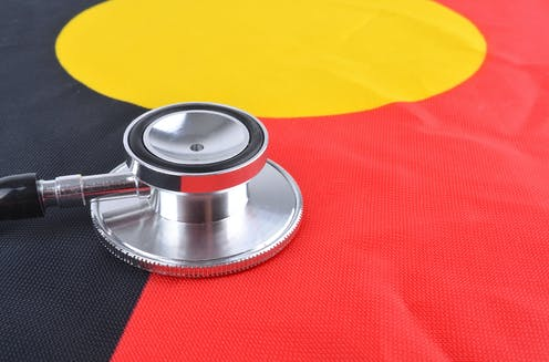 A stethoscope rests on the Aboriginal flag.