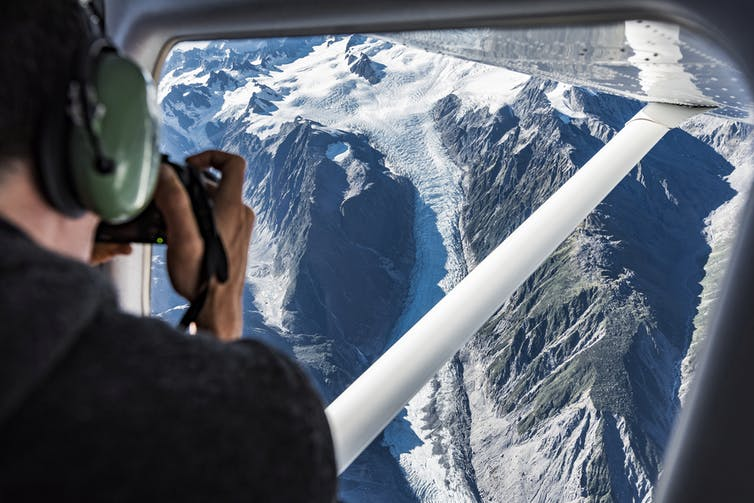 A person taking an image of a glacier