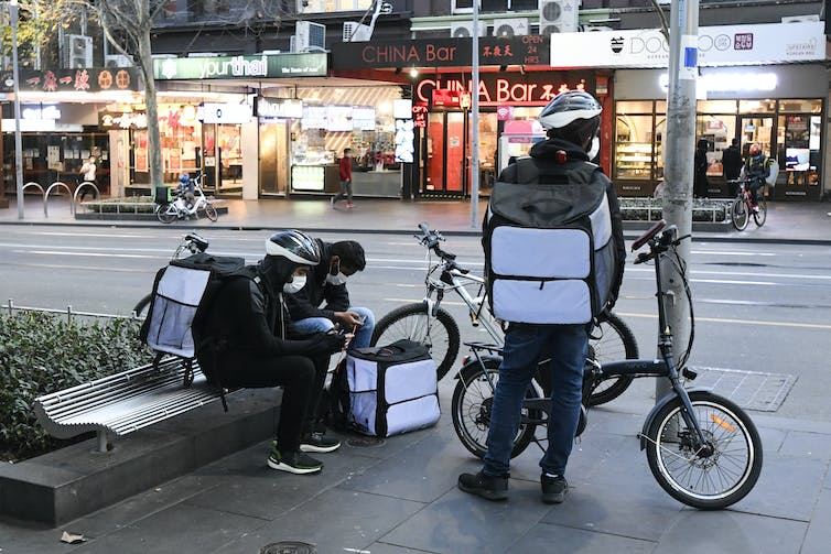 Delivery riders in Melbourne's deserted CBD