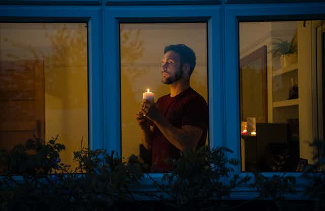 A man holds a candle at home in lockdown.