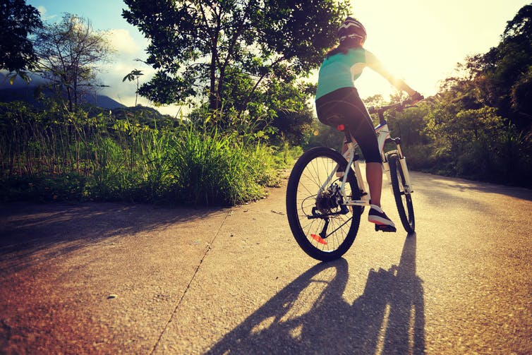 Female cyclist cycling on sunrise forest trail