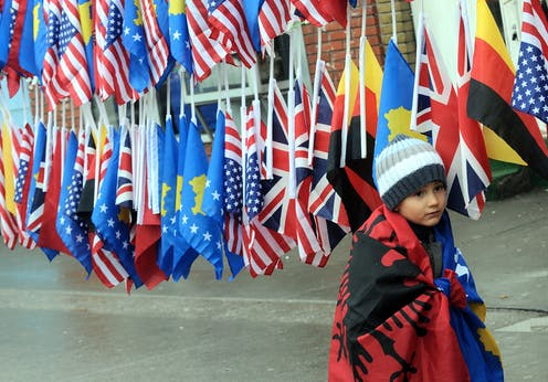 A boy wrapped in the Albanian and Kosovan flags in front of other national flags.