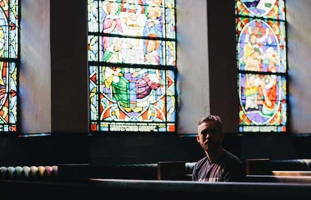 Un homme assis sur un banc d'église