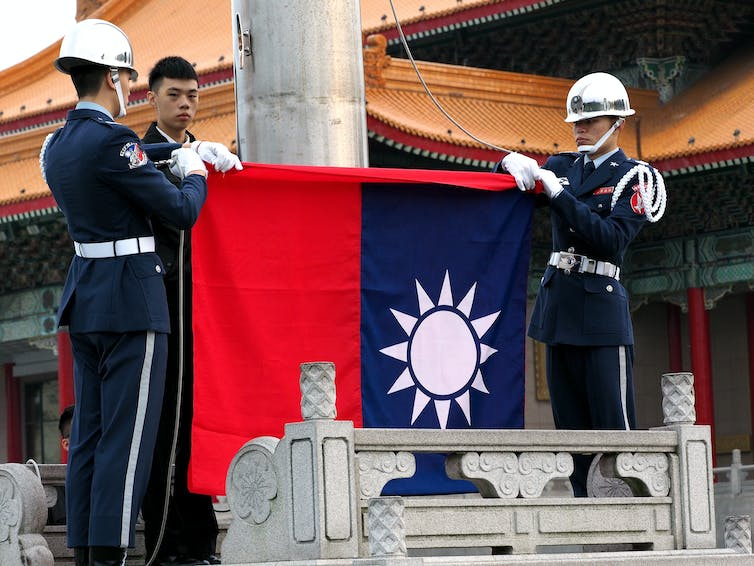 Men lower the Taiwanese flag.