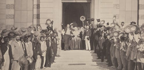 Hospital patients stood outside, raising their hats to celebrate a marble bust of Napoleon III.