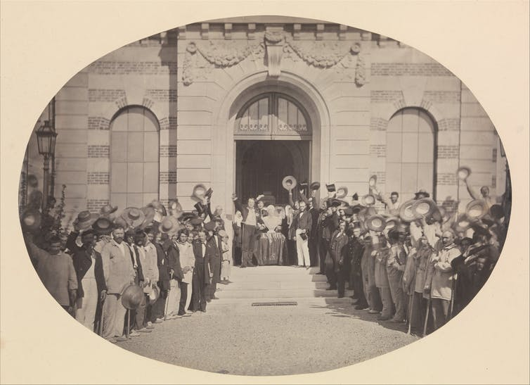 A photograph of hospital patients stood outside, raising their hats to celebrate a marble bust of Napoleon III.
