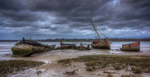 Several abandoned boats lie in the mud in a river estuary.