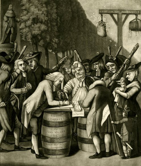A group of people assembled around a barrel signing a document.