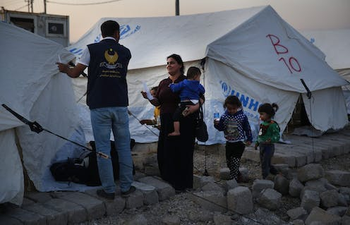 A mother with her children speaks to an aid worker in front of tents