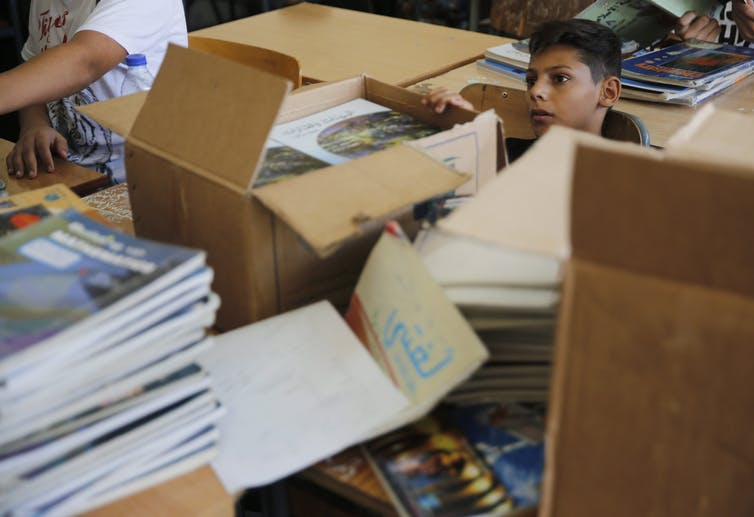 A schoolboy sits between boxes of new books in a classroom