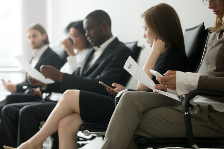 People in suits, sitting, waiting for job interviews
