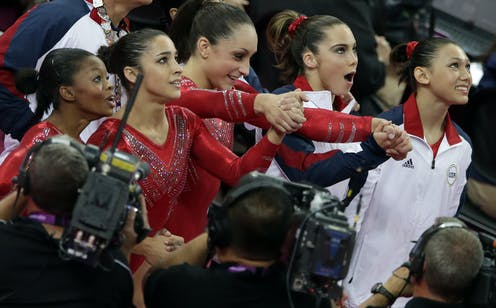 Five young gymnasts look up nervous and excited.