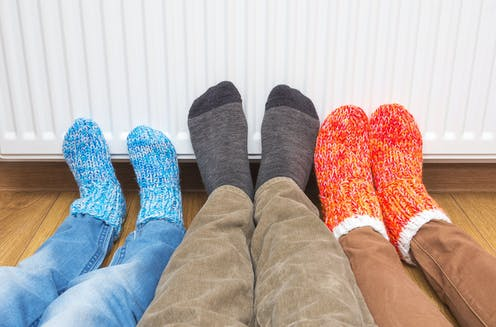 Three feet in woolly socks are against a heater keeping warm.