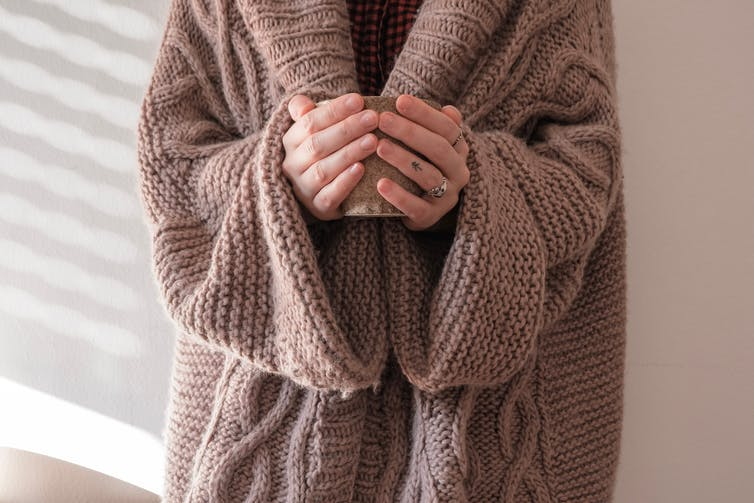 A person wearing a woolly coat holds a cup of tea.