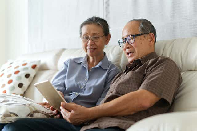 Older Asian couple sitting on the couch using tablet.