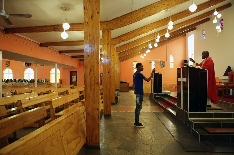 Parishionr holds up mobile phone to record priest conducting mass in an empty church