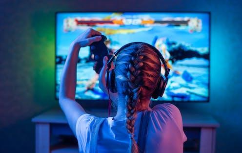 Una joven juega a videojuegos en una pantalla de televisión.