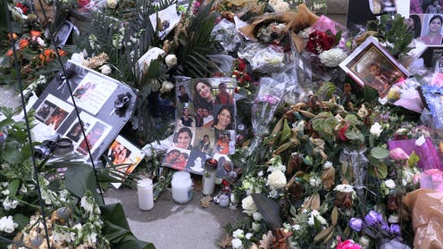 A memorial comprising photos of victims, flowers and candles on a pavement.