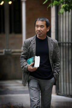 Japanese novelist Haruki Murakami walking holding a book.