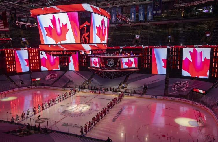 Hockey players stand before the national anthem; screens surrounding them display the Canadian flag.